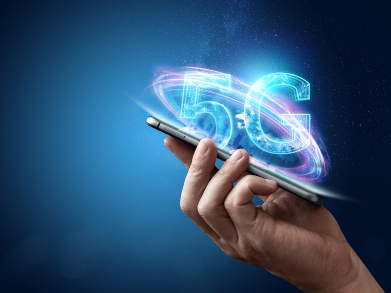 Person holding a phone with letters 5G coming out of it