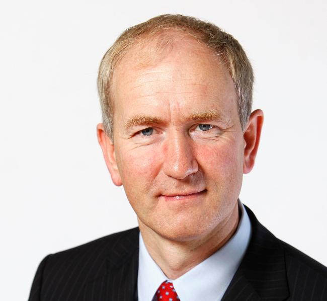 Man in dark suit with red tie.