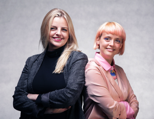Woman with blond hair and a woman with pink hair.