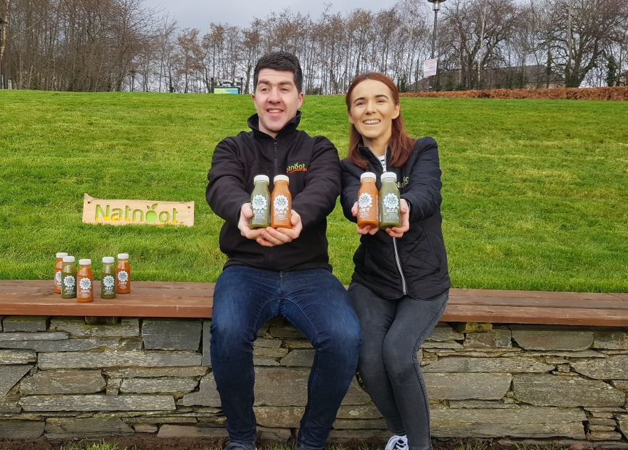 Man and woman sitting on a wall holding drinks.