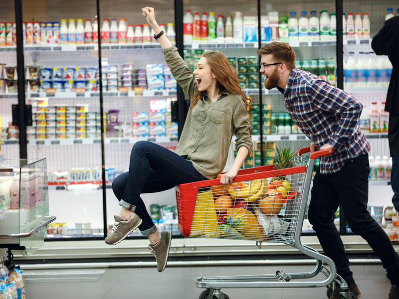 Young happy man pushing shopping cart with his girfriend inside.