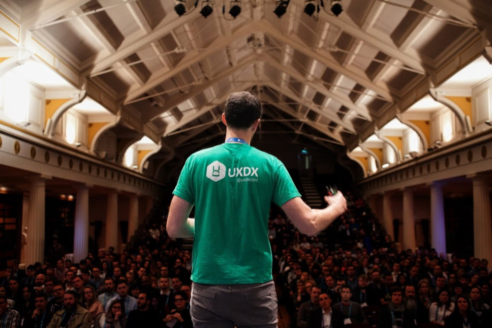 Man in green t-shirt addressing a crowd.