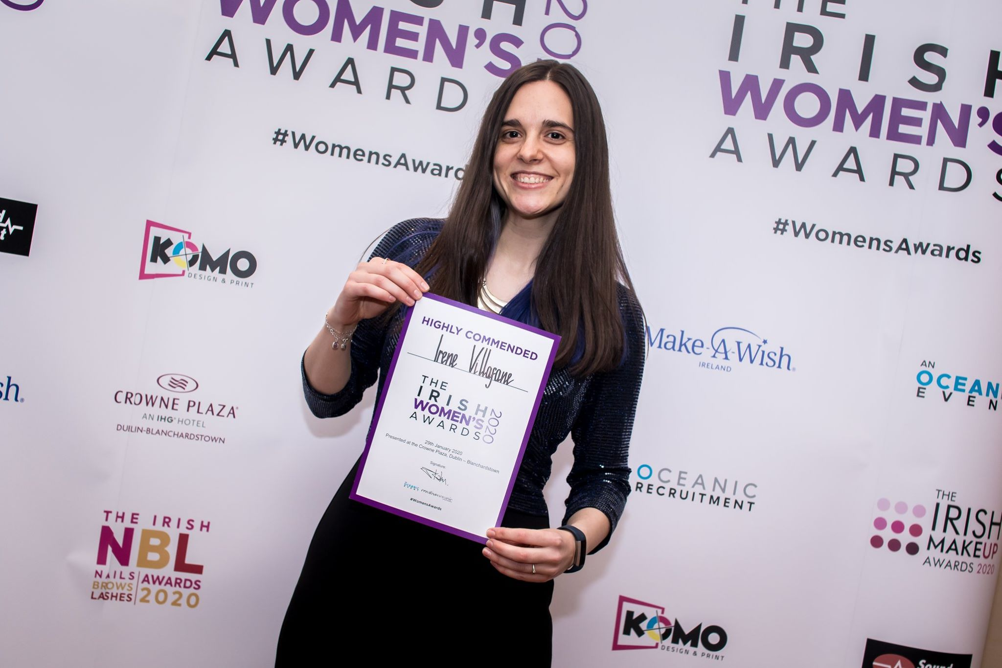 Dark-haired woman holding a certificate.