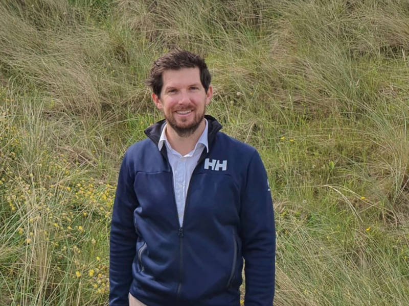 Man in blue jacket standing in a field.