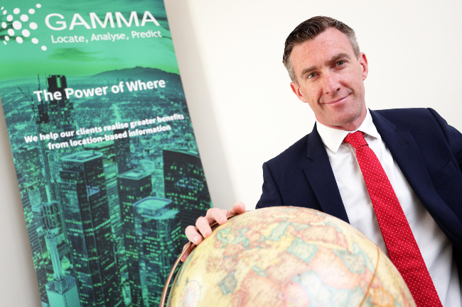 Man in red tie standing over globe.