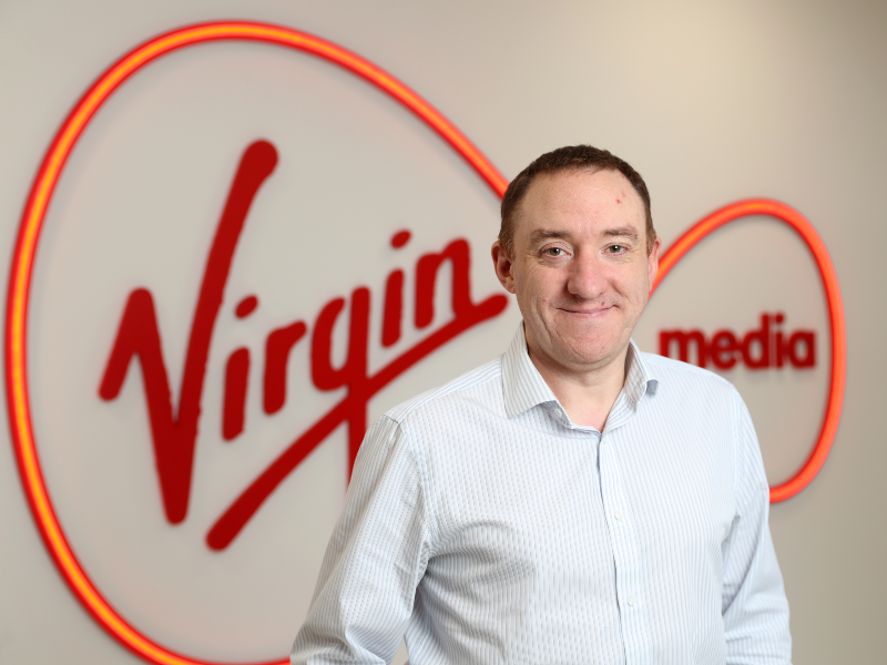 Dark-haired man standing in front of Virgin Media sign.