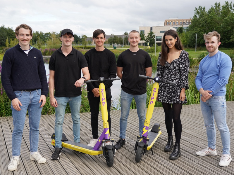 Group of people standing with 2 e-scooters.