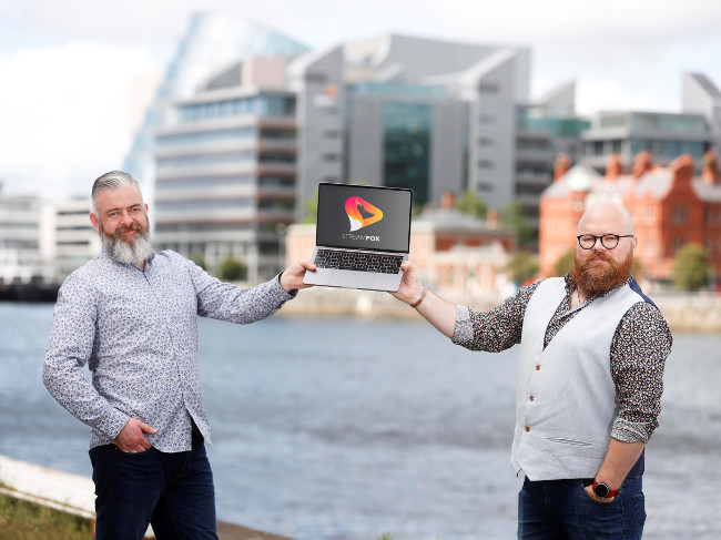 Two men holding a computer on Dublin docks.