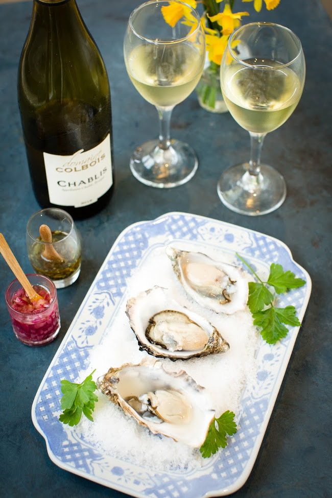 oysters on a plate beside glasses of white wine.