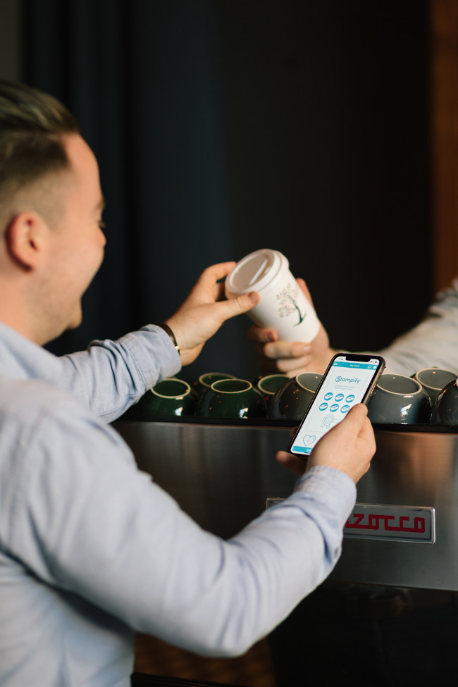Person paying for coffee with their smartphone.