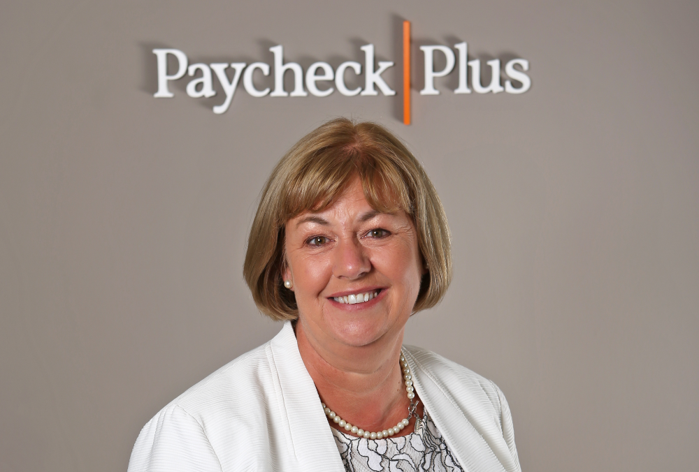 blonde-haired woman in white coat under sign Paycheck Plus.