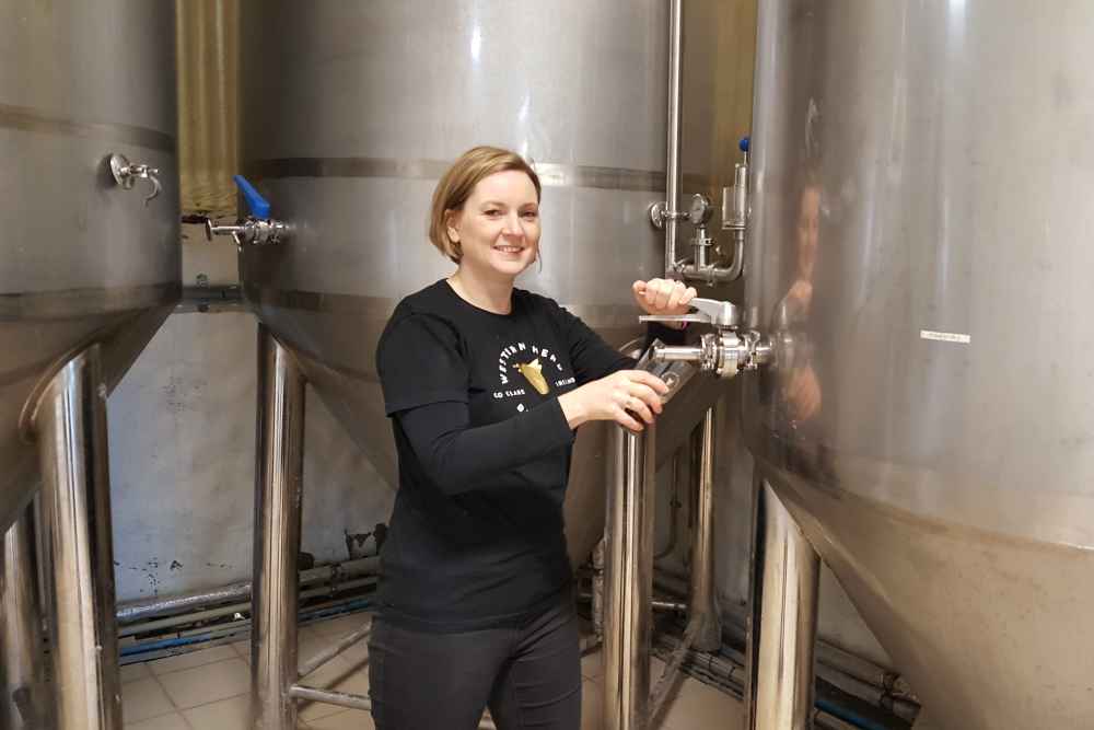 Woman pouring beer from a giant vat.
