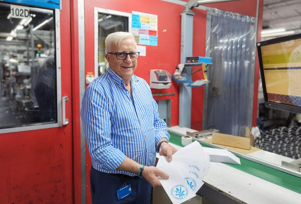 Man in blue shirt holding envelopes.