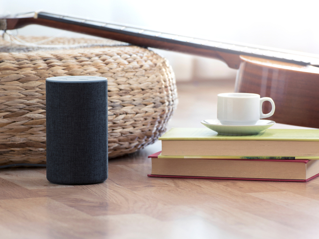 Alexa smart home speaker beside books and a cup of tea.