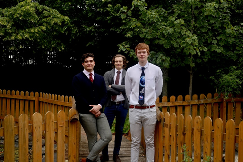 Three young men leaning on a fence.