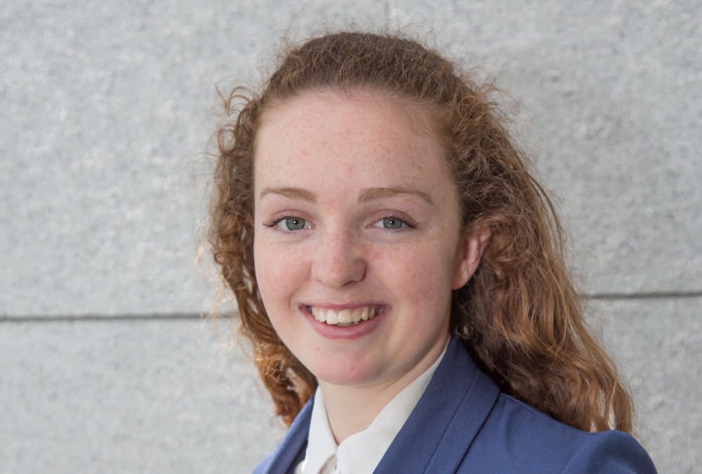 Young woman with red hair and wearing blue jacket and white blouse.