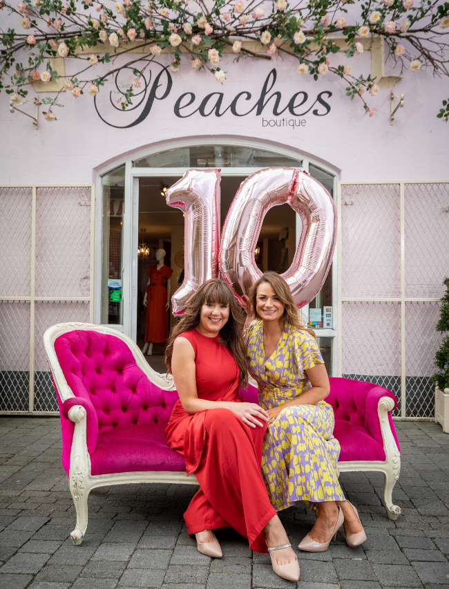 Two well-dressed women sit on a pink setee.