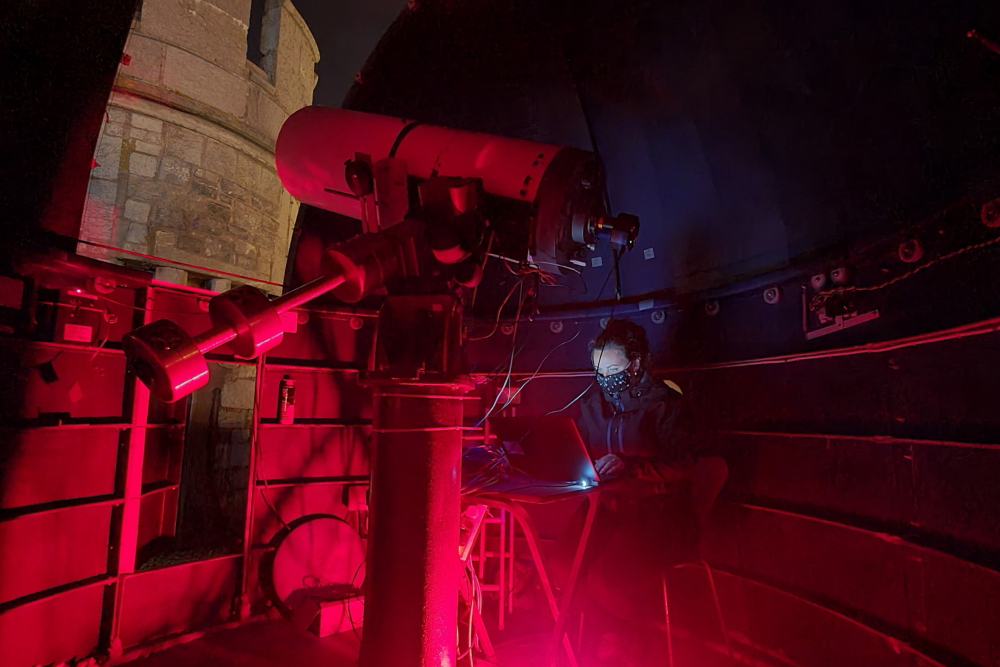 scientist working with telescope.