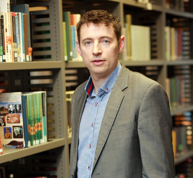 Dark-haired man standing in a library.