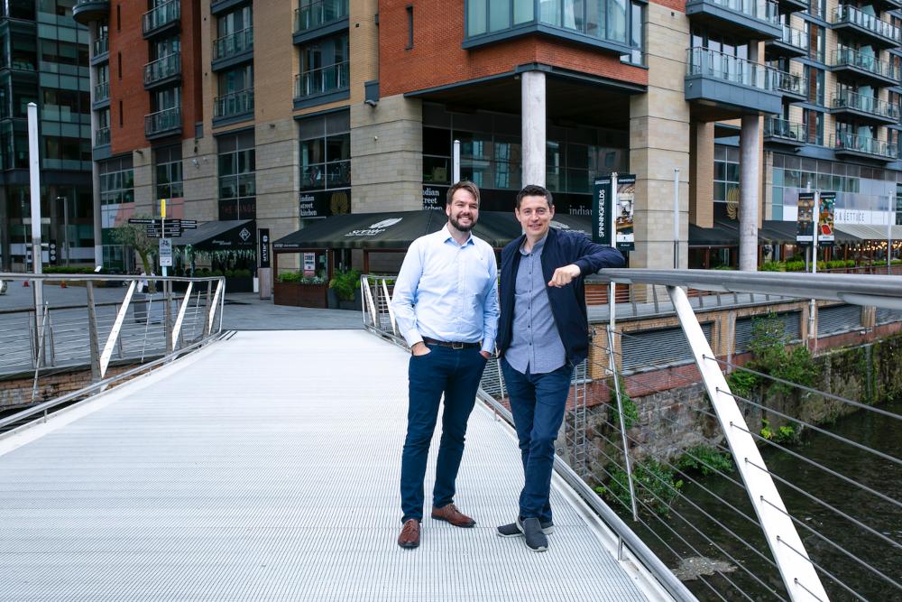 Two men standing on a bridge.
