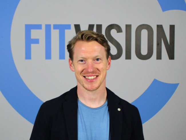 Fair-haired man in dark-jacket under a FitVision sign.