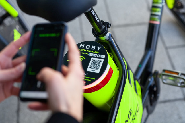 Person using smartphone to rent an electric bike.
