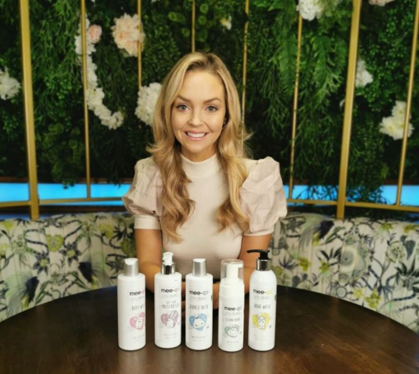 Woman with blonde hair behind a range of products.