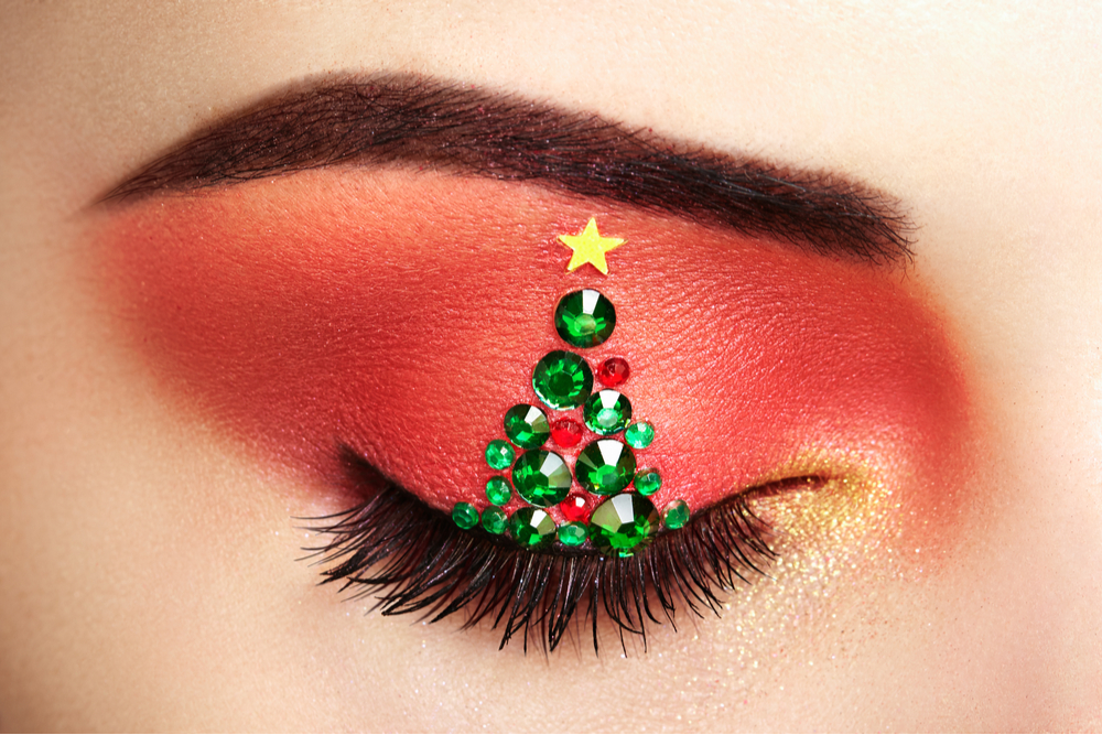 Woman in make-up with Christmas tree design.