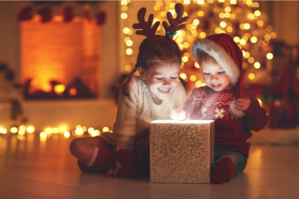 Children opening a gift at Christmas.