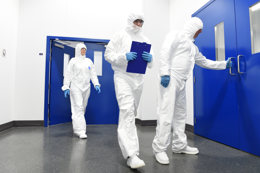 Pharma workers in white cleanroom suits.