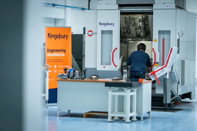 Man working with large 3D printing machine.