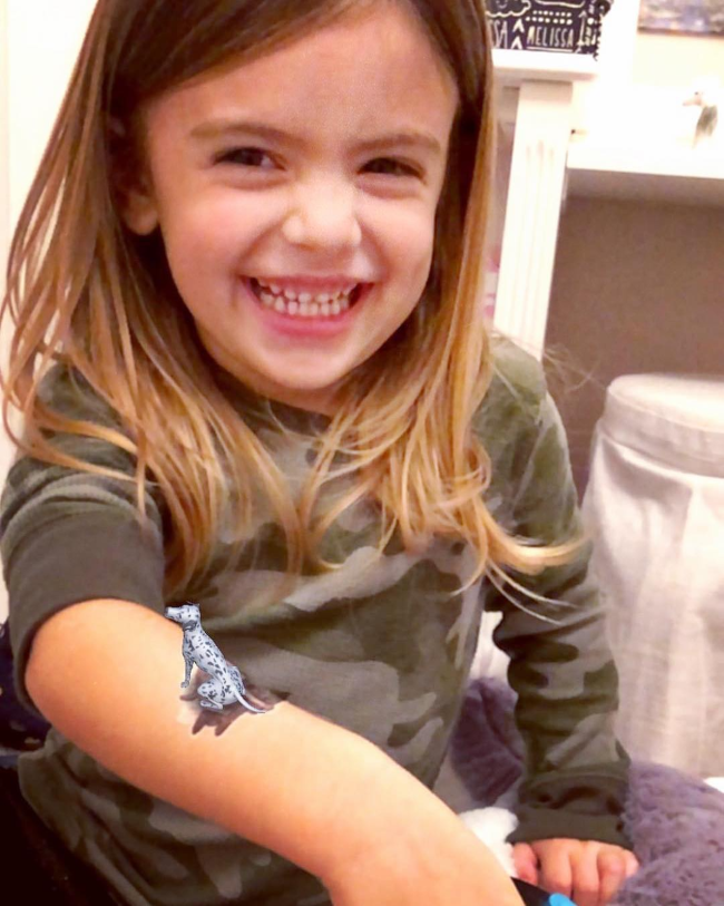Young girl with an augmented reality tattoo on her arm.