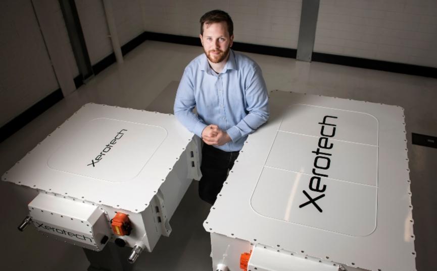 Man standing between two big batteries.