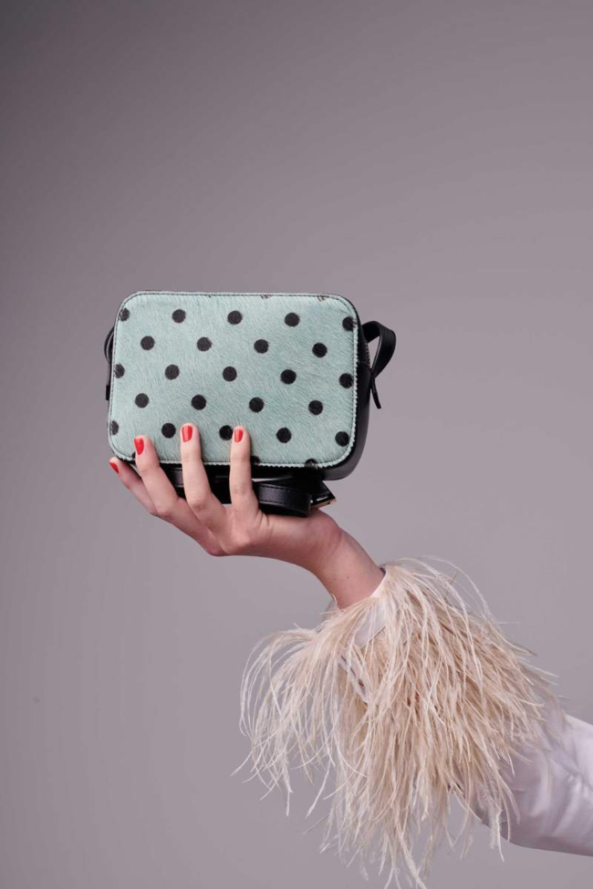 Woman's hand holding a pale blue handbag with spots.