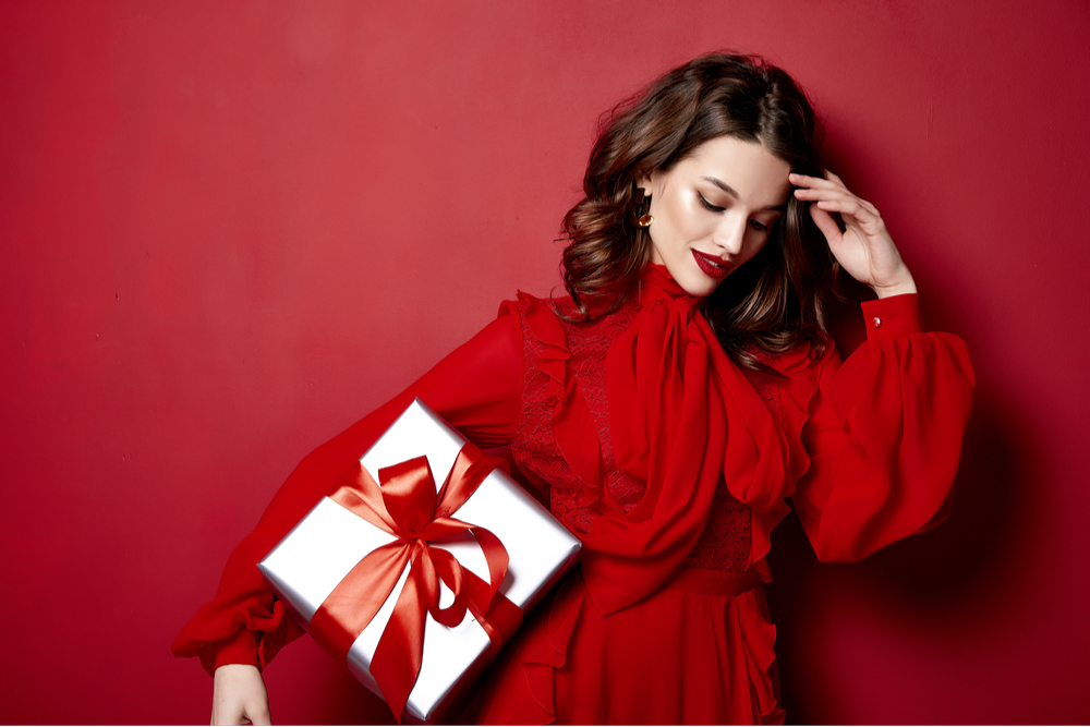 Woman in red dress holding a present.