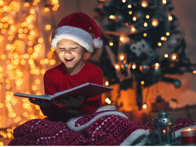 Kid reading a book at christmas.