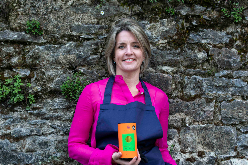 Woman in pink blouse, blue apron holding a box of biscuits.