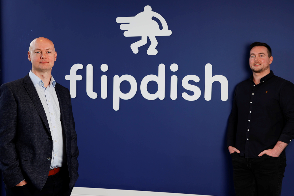 Two men standing by a sign saying Flipdish.
