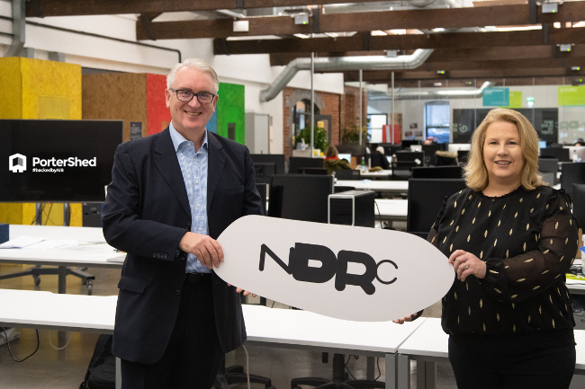 Man and woman holding NDRC sign.