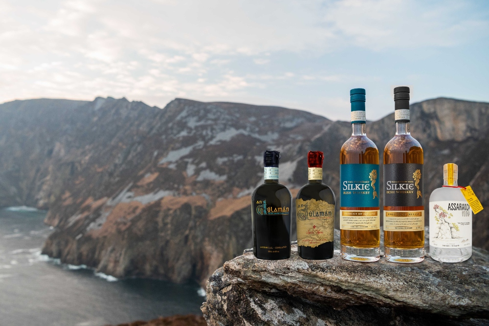 Bottles of whiskey in front of a sea cliff.