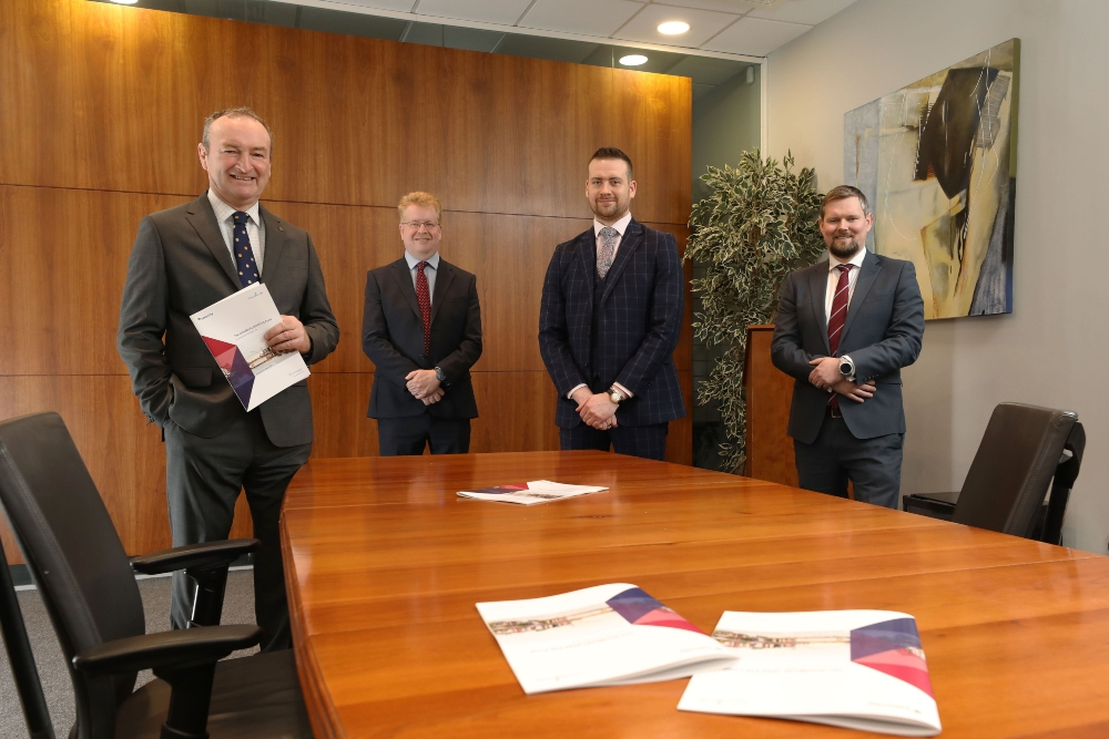 Four men standing at end of a boardroom table.