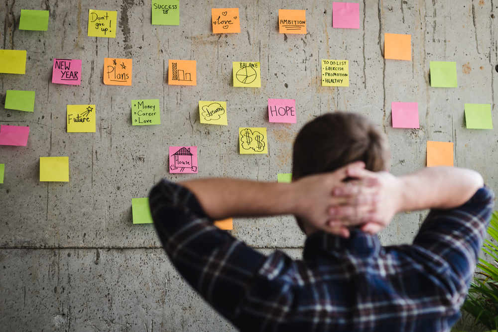 Entrepreneur looking at sticky notes on a wall.