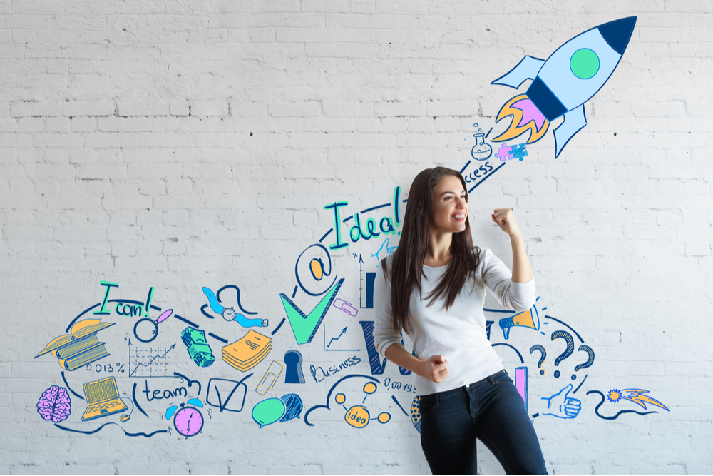 Woman entrepreneur standing before gravity of a rocket on a wall.