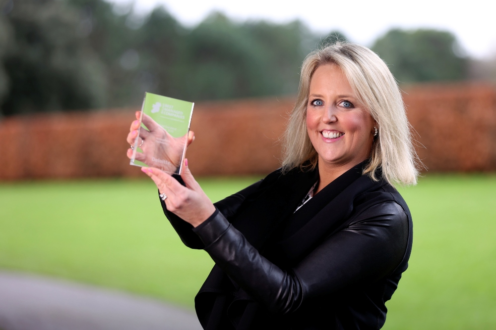 Blonde-haired woman with black jacket holding an award.