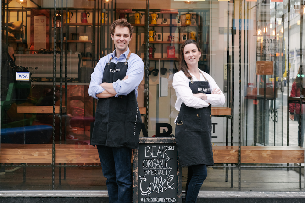 Man and woman standing with arms folded outside a coffee roastery in Dublin.