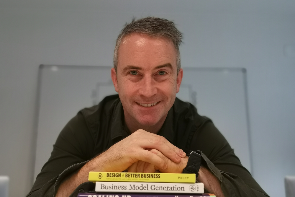Man in green shirt leaning on a pile of books.