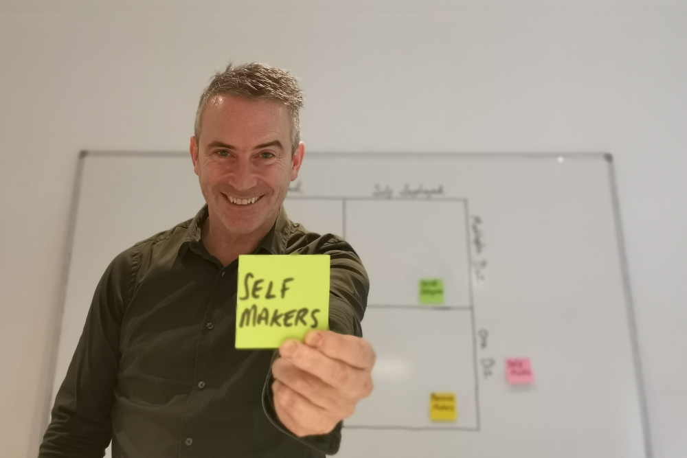 Man in green shirt holding a sticky note saying Self Makers.