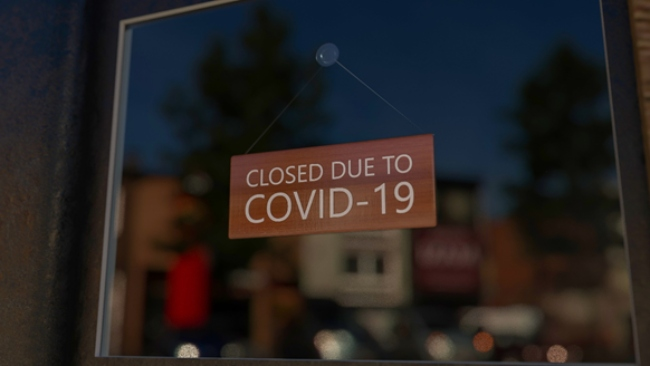 Closed sign in a window of a shop due to Covid.