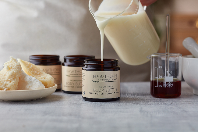 Pouring body butter into a jar.