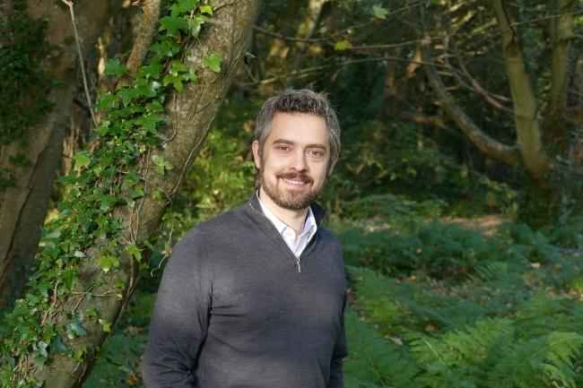 Man in grey jumper standing in woods.